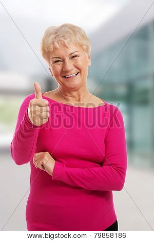 Old woman wearing pink shirt, showing OK