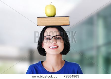 Smiling woman holding an apple on head