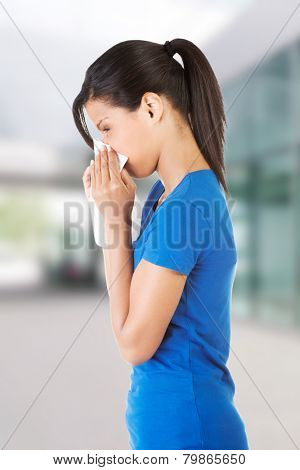 Allergic woman with tissue blowing her nose.