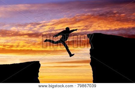 Man Jumping Across The Gap From One Rock To Cling To The Other. Man Jumping Over Rocks With Gap. Ele