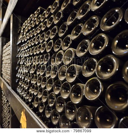 stacked up wine bottles in the cellar, dusty but tasty