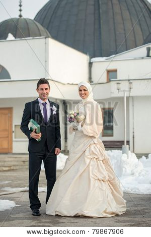 Just married muslim couple posing in front of mosque