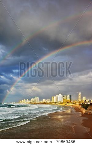 Storm and a rainbow in the Mediterranean. Promenade and a huge beach in Tel Aviv