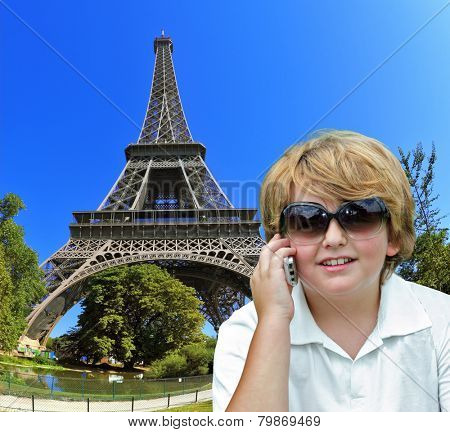Beautiful blond boy having fun chatting with friends on a cell phone. Background - the Eiffel Tower. The picture was taken Fisheye lens