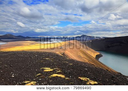 Iceland in July. The oval blue lake in a crater of the cooled-down volcano. Coast of the lake are from  red rhyolite