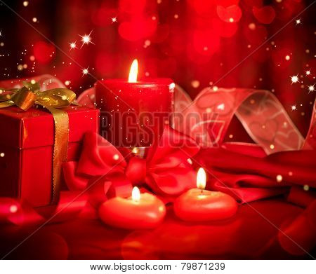Valentine's Day. Valentine Red Heart shaped candles and Gift on Red Silk Background. Beautiful Valentine card art design