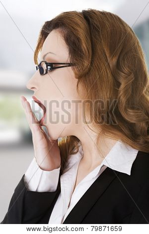 Tired sleepy beautiful businesswoman yawning
