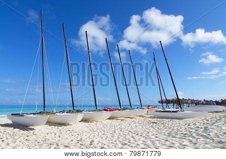 A Row Of Catamarans On White Sandy Beach