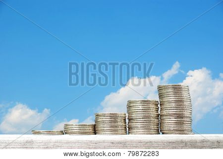 Business Concept With Stacks Of Coins Against Blue Sky Background