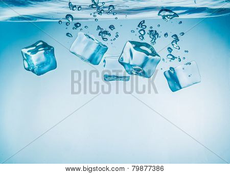 Ice cubes falling into the water sinking to the bottom. Abstract background.