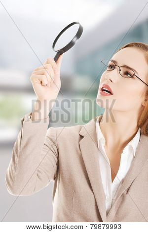 Beautiful caucasian business woman with magnifying glass