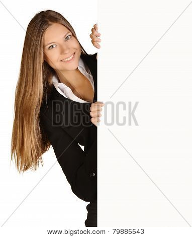 Business woman looks out from behind a blank white sheet of paper.