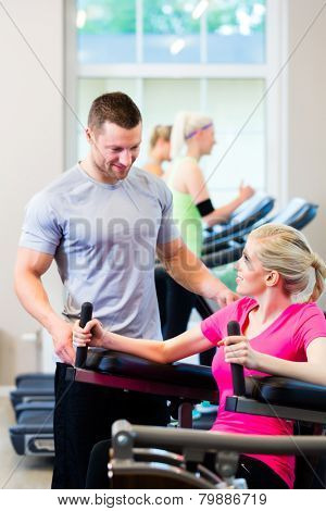 Woman with personal trainer doing sport in gym