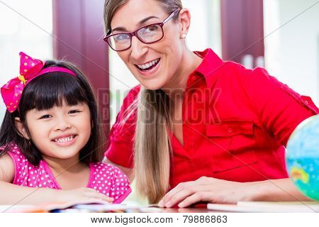 Teacher giving language lessons and doing homework to Chinese child