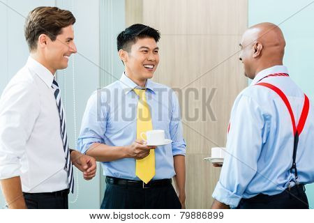 Business team of Indian, Chinese, and Caucasian men, at informal coffee meeting