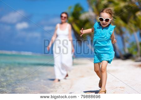 Beautiful family of mother and daughter enjoying vacation at tropical island