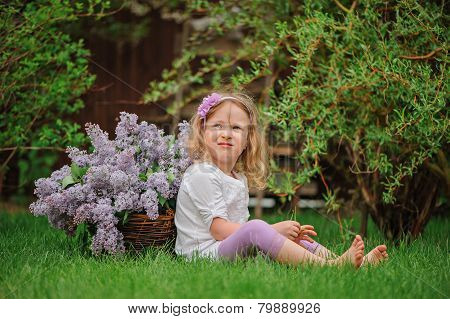 cute child girl in flower headband sitting in spring garden with basket with cut lilacs