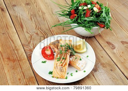 savory fish portion : roasted norwegian salmon chunks and vegetable salad on white dish over wooden table