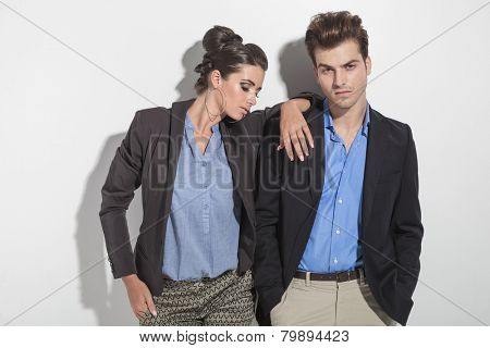Attractive young fashion man leaning on a wall with his hands in pockets while his girlfriend is looking down and holding her hand on his shoulder.