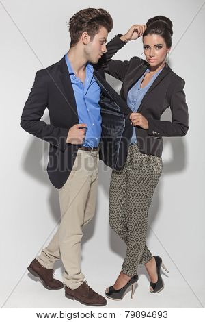 Full length picture of a casual couple posing together on studio background.  The woman is leaning her elbow on his shoulder while pulling his jacket.