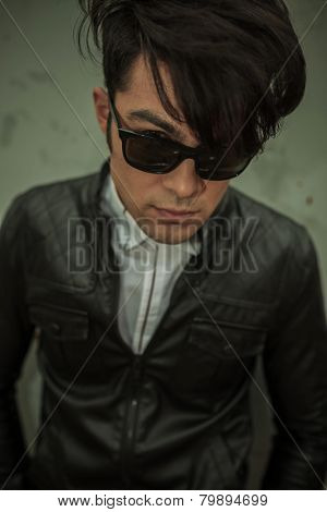Close up picture of a young fashion man wearing a leather jacket and sunglasses looking at the camera.
