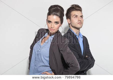 Attractive young man looking up with his arms crossed while his girlfriend is posing with her hands on her hips.