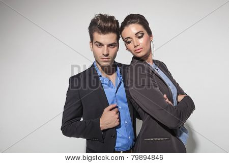 Attractive young fashion woman holding her arms crossed while looking down. Her lover is looking at the camera while fixing his jacket.