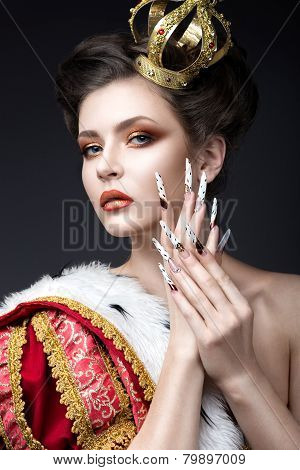 Beautiful girl in the image of the Queen in the mantle with a crown on the head and long nails. Beau