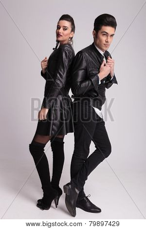 Full length picture of a fashion couple posing back to back. The man is fixing his collar while the woman si looking at the camera.