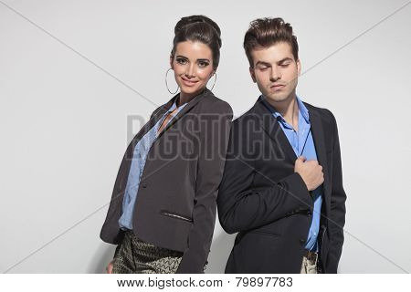 Young casual man posing with his eyes closed while his girlfriend is smiling at the camera.
