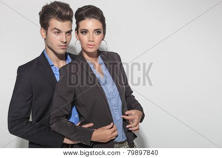 Picture of a young fashion couple posing together. The man is holding the woman from behind.