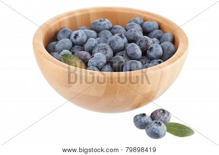Wooden bowl with bilberry berries