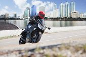 stock photo of motorcycle  - young man riding big bike motorcycle on city road against urban and town building scene background use for people and convenience vehicle to traveling in town - JPG