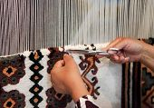 image of loom  - Woman working at the loom. Tunisian national carpet. Close up ** Note: Shallow depth of field - JPG