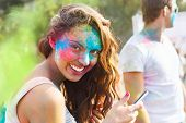 stock photo of holi  - Portrait of happy young girl on holi color festival using mobile phone - JPG