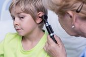 stock photo of otoscope  - Experienced female doctor examinating the kid by otoscope - JPG
