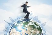 foto of unicycle  - Man riding unicycle around the globe with major cities concept - JPG