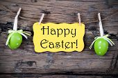 image of happy easter  - Yellow Easter Label With Happy Easter Hanging On A Line With Two Green Easter Eggs On Wooden Background Vintage 