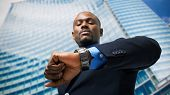 stock photo of punctuality  - Handsome businessman looking at his watch - JPG
