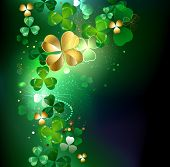 stock photo of four leaf clover  - gold clover with four leaves on a dark glowing background - JPG