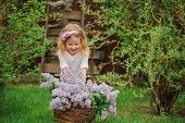 pic of headband  - horizontal portrait of cute child girl in flower headband playing in spring garden with basket of lilacs - JPG