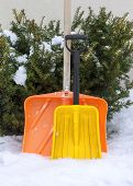 stock photo of snow shovel  - Two snow shovels on snow outside house - JPG