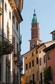 picture of vicenza  - Bottom perspective of the famous Clock Tower of Vicenza seen from one of the town streets with some old palaces in the foreground - JPG