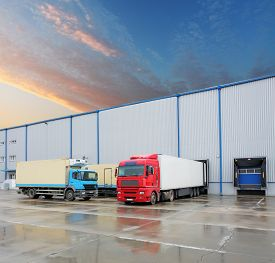 pic of trucks  - Cargo truck at warehouse building at sunset - JPG