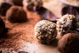 stock photo of bonbon  - Assorted dark chocolate truffles with cocoa powder biscuit and chopped hazelnuts over baking paper selective focus close up - JPG