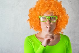 image of shhh  - Beautiful young adult woman with orange wig and green eyes making Shhh sign with finger on Lips - JPG