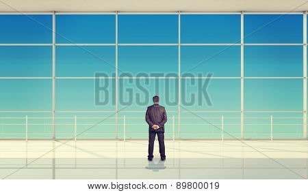 Businessman with hands behind in front of window