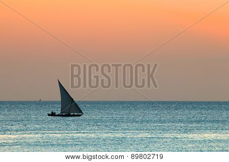 Silhouette of a small sailboat (dhow) on water at sunset, Zanzibar island