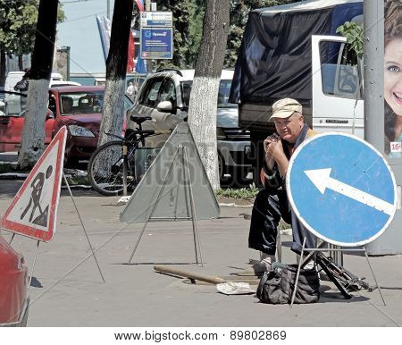 Workman Near An Open Hatch And Surrounded By Road Signs
