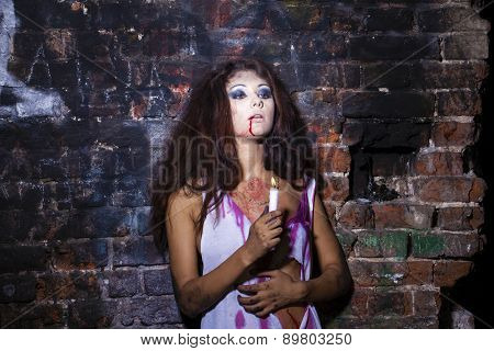 Frightened girl with a candle in hands on dark brick wall